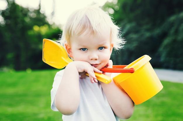 자연 배경에 모래 장난감을 가진 귀여운 사랑스러운 금발 소년의 초상화