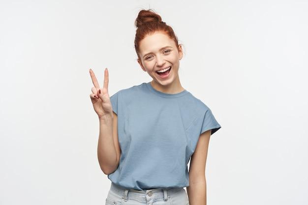 Портрет милой, взрослой рыжей девушки с волосами, собранными в пучок. в синей футболке и джинсах. показывая знак мира, наклонила голову и улыбнулась. изолированные над белой стеной