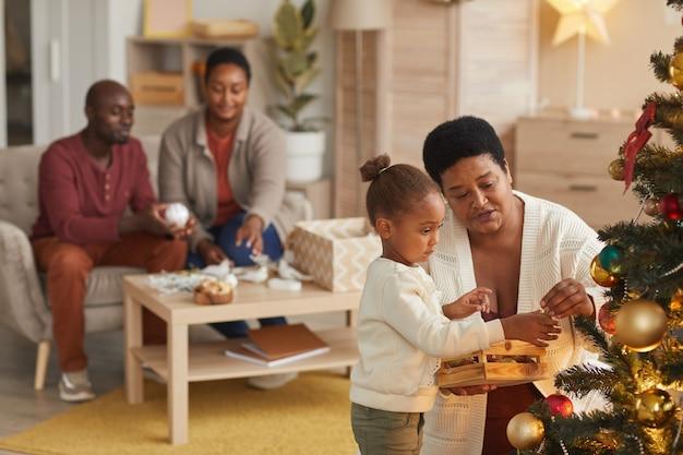 家でホリデーシーズンを楽しみながら、祖母と幸せな家族と一緒にクリスマスツリーを飾るかわいいアフリカ系アメリカ人の女の子の肖像画