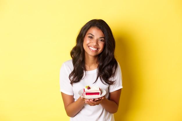 Портрет милой афро-американской девушки, держащей кусок торта и улыбающейся, стоящей на желтом фоне