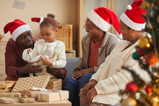 집에서 휴가 시즌을 즐기면서 모든 산타 모자를 쓰고 가족과 함께 크리스마스 선물을 여는 귀여운 아프리카 계 미국인 여자의 초상화