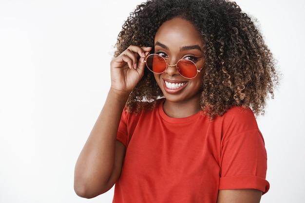 Портрет милой афро-американской современной женщины в красной футболке и модных солнцезащитных очках, беззаботно трогающей ободок и смотрящей в восторге от нежности впереди с хорошим настроением над белой стеной