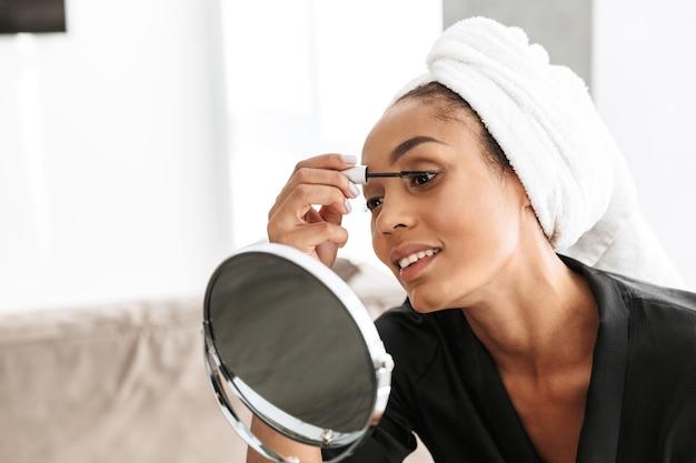 自宅の鏡にマスカラを適用する白いタオルに包まれたバスローブを着たかわいいアフリカ系アメリカ人女性の肖像画