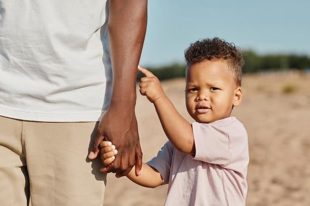 太陽の下でビーチで散歩を楽しみながらお父さんと手をつないでかわいいアフリカ系アメリカ人の幼児の肖像画...