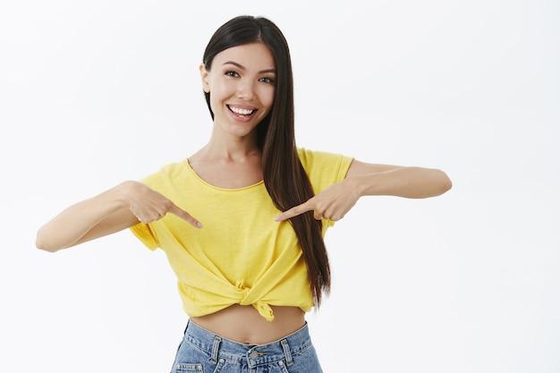 노란색 티셔츠에 화장이없는 귀엽고 여성스러운 아시아 여자의 초상화는 독단적이고 친절한 손가락으로 가리키는 미소
