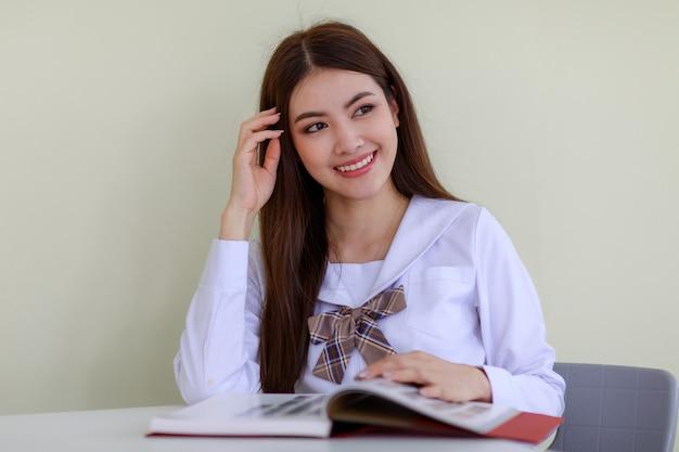 귀엽고 젊은 아시아 소녀, 라오스 민족의 초상화, 일본, 한국 스타일의 여학생 교복을 입고, 앉아서 행복한 얼굴로 책을 읽고 있습니다. 학교와 대학 공부 개념입니다.