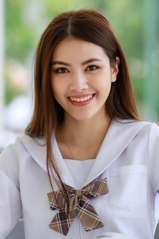 귀엽고 젊은 아시아 소녀, 라오스 민족의 초상화는 일본, 한국 스타일의 여학생 교복을 입고 앉아 포즈를 취하고 쾌활하고 자신감 있게 카메라에 미소를 짓고 있습니다.