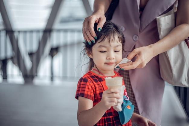 야외 아이스크림을 먹는 귀여운 아시아 여자의 초상화. covid-19 대유행 동안의 삶.