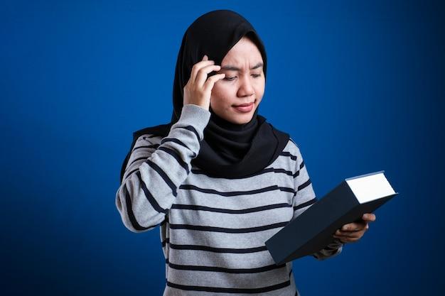 Портрет милой азиатской мусульманской женщины, больной и уставшей, читающей слишком много книг на синем фоне