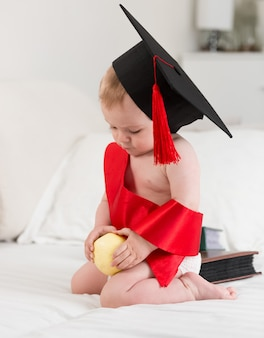 リンゴを保持している卒業帽のかわいい男の子の肖像画。赤ちゃん教育の概念