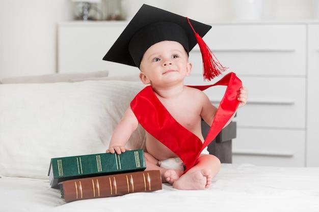 Портрет милого мальчика в выпускной, сидя с книгами на диване