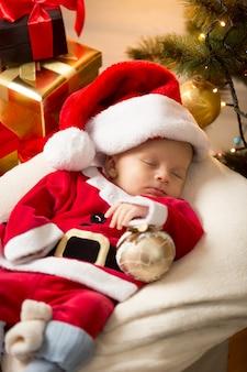 Портрет милого мальчика в костюме санты, спящего до рождественских подарков