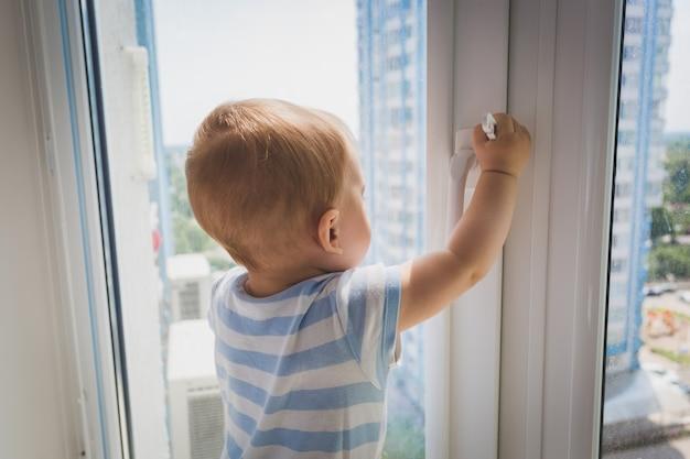 窓のハンドルを引っ張るかわいい男の子の肖像画。危険にさらされている子供の概念