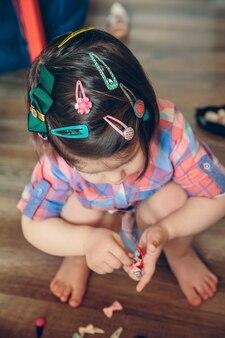 自宅の木の床の上で遊んでいるヘアクリップがたくさんあるかわいい女の赤ちゃんの頭の肖像画。頭に選択的に焦点を当てます。