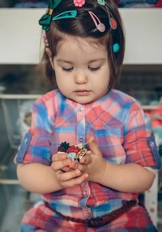 집에서 나무 바닥 위에 손에 많은 머리핀을 가지고 노는 귀여운 여자 아기의 초상화. 헤어 클립에 선택적 초점입니다.