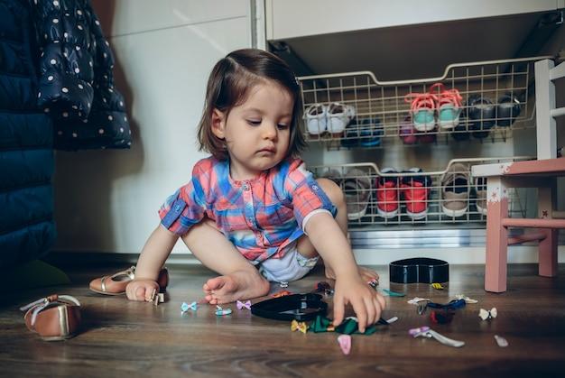 집에서 나무 바닥에 앉아 머리 클립 컬렉션을 가지고 노는 귀여운 여자 아기의 초상화