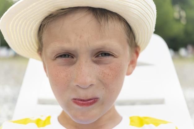 そばかすのクローズアップと帽子のかわいい、美しい少年の肖像画。真面目で悲しげな表情と美しい瞳の少年。学生、男子生徒、学校の休み。日焼け止めの広告。美しいそばかす。