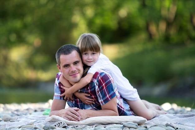 背景のボケ味の緑の木々の明るい夏の日に小石の川の土手に若い父親を抱いてかわいいブロンドの女の子の肖像画。幸せな家族関係、愛、ケア、完璧な休日のコンセプトです。