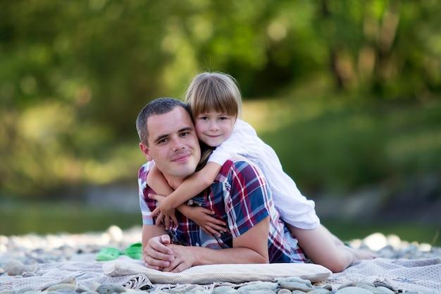 ぼやけている緑の木々の明るい夏の日に小石の川の土手に若い父親を抱いてかわいいブロンドの女の子の肖像画。幸せな家族関係、愛、ケア、完璧な休日のコンセプトです。