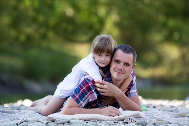 若い父親を抱いてかわいいブロンドの女の子の肖像画