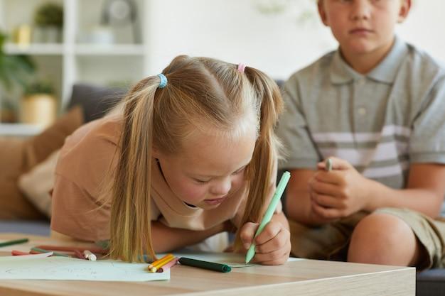 Портрет милой блондинки с синдромом дауна, пишущей или рисующей, наслаждаясь развивающими упражнениями дома, скопируйте пространство