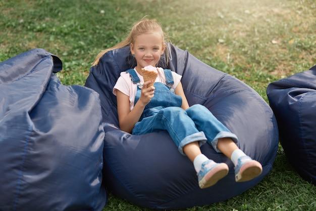 포니 테일 귀여운 금발 소녀의 초상화, 흰색 셔츠와 데님 바지를 입고, 틀 의자에 앉아 아이스크림을 먹고