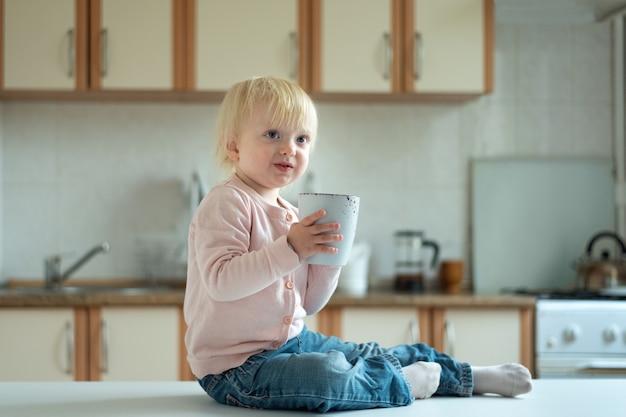큰 컵으로 부엌에 있는 귀여운 금발 2살짜리 아이의 초상화.
