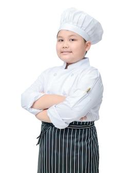 料理の帽子とエプロンスタンドと白い背景に笑顔でかわいい男の子のシェフの肖像