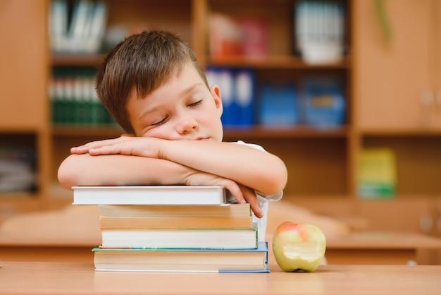 Портрет милого мальчика на вершине книжного стога. концепция обучения в начальной школе.