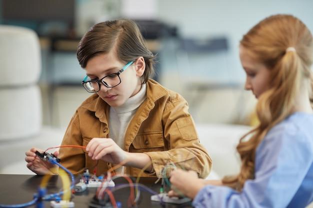学校の工学の授業中にロボットを構築しながら眼鏡をかけ、電気回路を実験しているかわいい男の子の肖像画