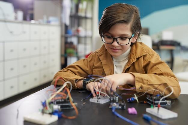開発学校の工学の授業中にロボットを構築しながら眼鏡をかけ、電気回路で作業しているかわいい男の子の肖像画