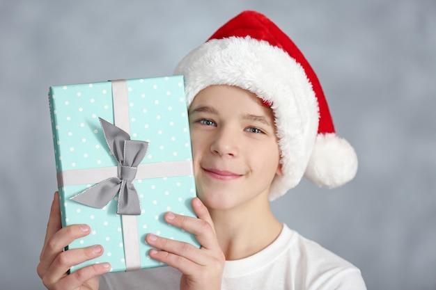 파란색 선물 상자를 가진 귀여운 소년의 초상화를 닫습니다.