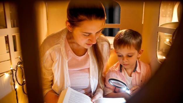 잠들기 전에 텐트나 장난감 집에서 큰 책을 읽는 어린 모터를 가진 귀여운 소년의 초상화. 아동 교육과 가족이 밤에 함께 시간을 보내는 개념.