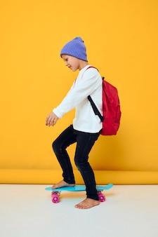 かわいい男の子の肖像画は青い帽子の子供の頃のライフスタイルの概念でスケートボードに乗る