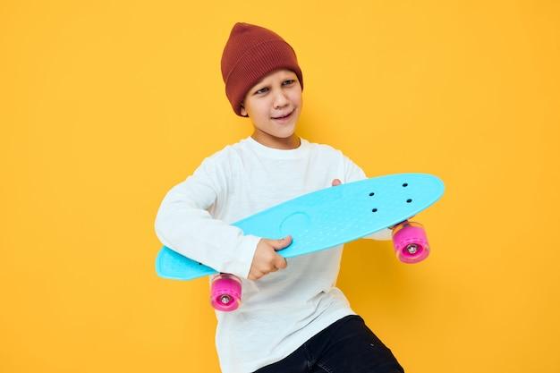 빨간 배낭 블루 스케이트보드 고립 된 배경을 가진 귀여운 소년의 초상화
