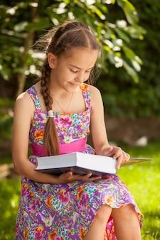 Портрет милой брюнетки, читающей большую книгу в лесу