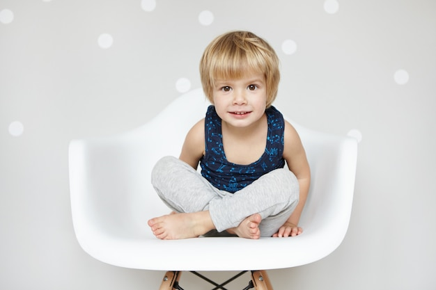 Портрет милого кавказского младенца со светлыми волосами и большими красивыми глазами, одетого в спальный костюм, сидящего со скрещенными ногами на белом стуле, смотрящего и улыбающегося, отказывающегося ложиться спать