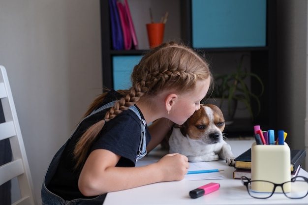 집에서 치와와 강아지와 함께 공부하는 귀여운 백인 빨간 머리 소녀의 초상화는 원격 교육 개념인 탁자에 앉아 있습니다. 아이가 개에게 키스합니다. 개는 숙제를 도와줍니다. 학교 개념으로 돌아가기.