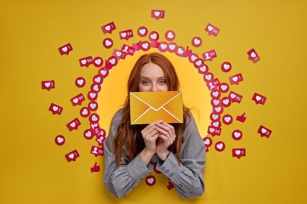 노란색에 고립 된 손에 편지 메시지를 들고 귀여운 백인 빨간 머리 여자의 초상화