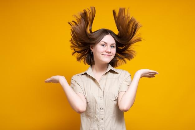 Портрет милой кавказской улыбающейся девушки, пораженной, показывая волнение, волосы развеваются на ветру. изолированные на желтом фоне