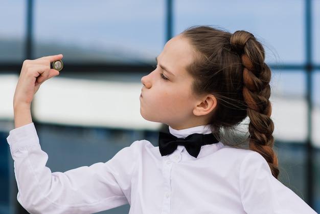 동전을 들고 귀여운 백인 십 대 소녀의 초상화입니다. 돈과 비즈니스 개념을 저장합니다.