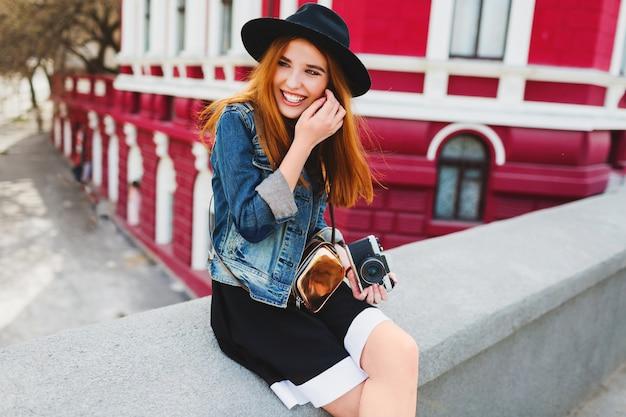 レトロなフィルムカメラを保持している路上でポーズ素晴らしい赤い髪のかわいい陽気な若い女性の肖像画