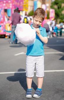 Портрет милого ребенка, едящего сладкую вату на фоне фестиваля летней ярмарки