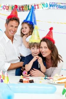 Портрет милых детей с родителями во время празднования дня рождения
