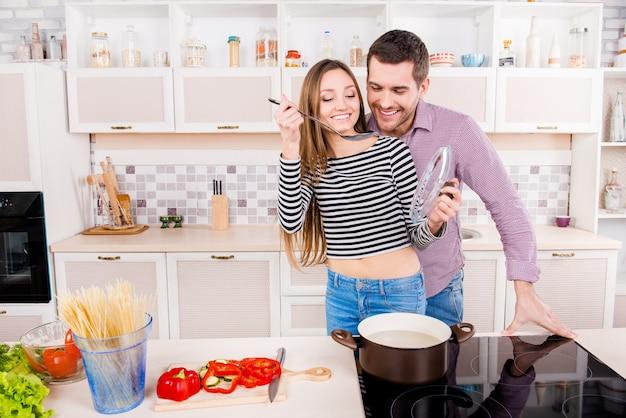 キッチンで温かい食事を冷やす愛のかわいいカップルの肖像画