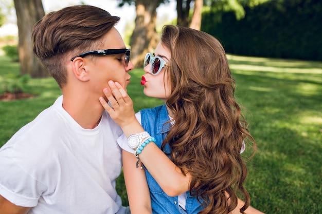 Портрет милой пары молодых людей на траве в парке. красивая девушка с длинными вьющимися волосами целуется с красивым парнем в белой футболке.