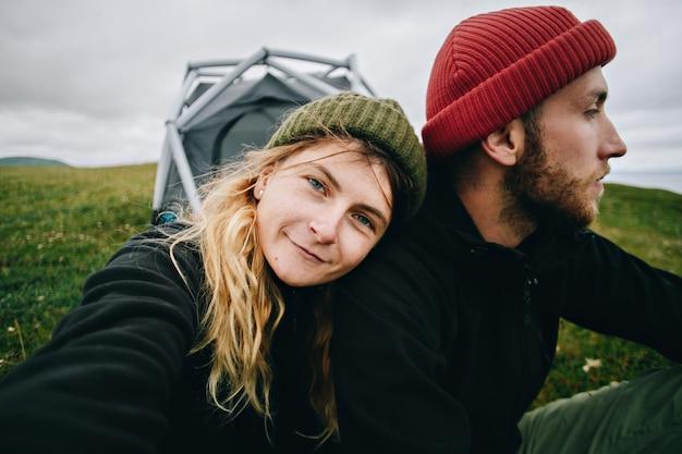 かわいいカップルの肖像画はテントの隣に座っています