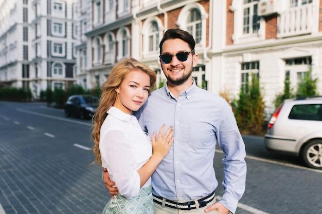 Портрет милой пары, гуляющей по британскому кварталу. красивый парень в солнечных очках обнимает блондинку с длинными волосами и улыбается, она серьезно смотрит.