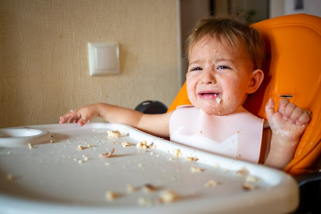 ダイニングテーブルと一緒に座っているかわいい泣いている赤ちゃんの幼児の肖像画