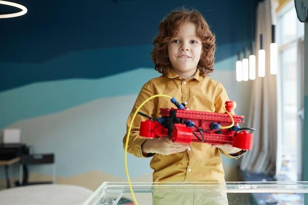 Портрет симпатичного кудрявого мальчика, опускающего роботизированную лодку в воду во время экспериментов с технологиями в лаборатории робототехники в школе, копирование пространства